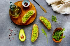 Avocado toasts with arugula. Flat lay. Good fats raw healthy eating concept royalty free stock images