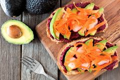 Avocado toasts with beet hummus, radishes & carrots, overhead on wood Royalty Free Stock Photography
