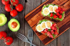 Avocado toasts with eggs and tomatoes, top view table scene Stock Photos