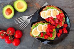 Avocado toasts with eggs and tomatoes, top view table scene Stock Photo