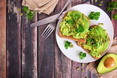 Avocado toasts with pumpkin and chia seeds, top view corner border against dark wood royalty free stock photo
