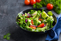 Avocado, tomato and arugula salad. Healthy vegan food. royalty free stock photography