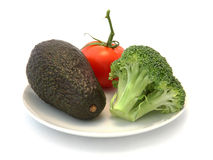 Avocado, Tomato and Brocolli. Small group of vegetables with broccoli, avocado and tomato on a white plate with a white background Royalty Free Stock Photography
