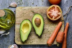 Avocado, tomato, carrot, garlic and olive oil Royalty Free Stock Image