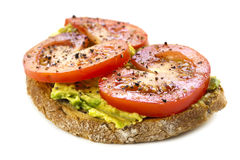 Avocado and Tomato Open Sandwich over White. Open sandwich topped with avocado, tomato, and ground pepper.  Isolated on white background Stock Images