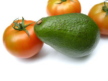 Avocado with tomatoes. A big complete green ripe avocado fruit with red tomatoes isolated on white studio background Stock Photo
