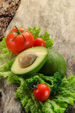 Avocado, tomatoes, lettuce, broccoli on wooden board. Royalty Free Stock Photography