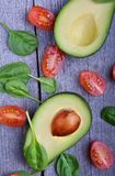 Avocado with tomatoes and spinach. On the wooden table Royalty Free Stock Photos