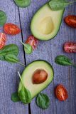 Avocado with tomatoes and spinach. On wooden table Stock Image
