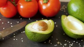 Avocado close up on the kitchen. Avocado and tomatoes on wooden table stock footage