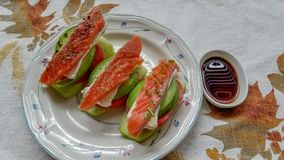 Avocado topped with tomato, brie cheese and cold smoked salmon lox, garnished with fresh chives and black pepper stock photo
