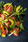 Avocado and trout salad on the black stone vertical top view. Salad with avocado , trout and asparagus on the black stone  vertical top view Stock Photography