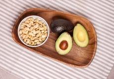 Avocado und Acajounüsse auf hölzerner Platte Lizenzfreie Stockbilder