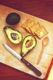 Avocado und Cracker auf einem hölzernen Brett Lizenzfreie Stockfotos