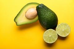 Avocado und Kalk auf gelbem Hintergrund Lizenzfreies Stockfoto