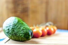 Avocado- und Kirschtomaten auf hölzernem Hintergrund lizenzfreie stockfotos