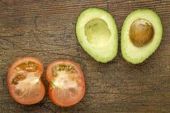 Avocado und Tomate geschnitten zur Hälfte Lizenzfreies Stockbild