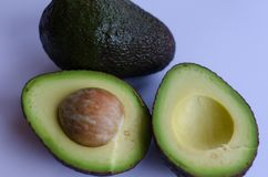 Avocado on white background. An halved and a whole `Hass ` avocado on white background royalty free stock photo