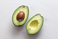 Avocado on a white wood background. Two halves of avocado and kernel, nut. Vegetarianism and healthy nutrition stock image