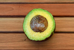 Avocado on a wood table. Half of an avocado on a wood table Stock Photo