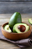 Avocado in a wooden bowl stock photography