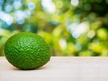 Avocado on wooden floor over green nature bokeh Stock Photo