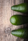 Avocado on the wooden table top view. Vertical Stock Photo