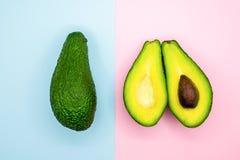 Avocadohälfte auf minimaler Nahrung des Blau- und Rosahintergrundes stockfotografie