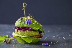 Avocadohamburger met groen pasteitje stock foto
