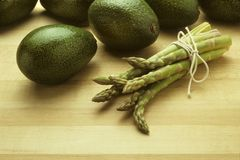 Avocados and asparagus on butcher block Royalty Free Stock Images