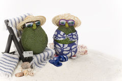 Avocados at Beach. Two avocados in miniature beach scene, including towels, chair and camera. One avocado relaxing in beach chair and one standing on sand, both Stock Images