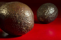 Avocados. Close up of ripened avocados on a red table royalty free stock photography