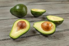 Avocados cut in half seed visible, one whole green pear in background, on gray wood desk.  stock photo