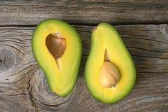 Avocados eine geschnitten in zwei mit Samen Lizenzfreie Stockfotos
