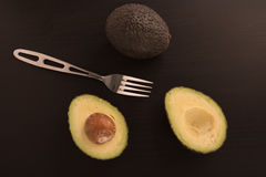 Avocados with a fork on  black background. Stock Photos