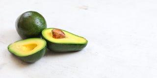 Avocados, jeden cały, inny cięcie w połówce, nasieniodajny widoczny na białej desce Szeroki sztandar z przestrzenią dla teksta na zdjęcia royalty free