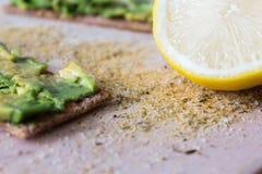 Avocados mit Zitrone auf einem hackenden Brett Lizenzfreies Stockfoto