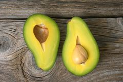 Avocados one cut in two with seed. On wooden surface Royalty Free Stock Photos