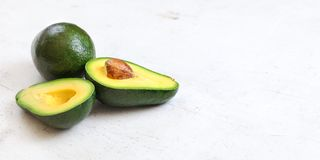 Avocados, one whole, other cut in half, seed visible on white board. Wide banner with space for text on right side.  royalty free stock photos