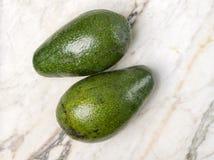 Avocados. Two avocado fruits, perfect for a ketogenic meal Stock Photos