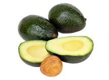Avocados on white, cut and whole with pit. Royalty Free Stock Photos