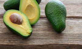Avocados on a wooden background Stock Images