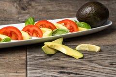 Avocadosalat auf einer weißen Platte und einem Holztisch Lizenzfreies Stockbild