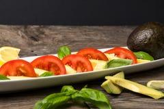 Avocadosalat auf einer weißen Platte und einem Holztisch Lizenzfreies Stockfoto