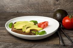 Avocadosandwich auf einer weißen Platte und einem Holztisch Lizenzfreie Stockfotografie