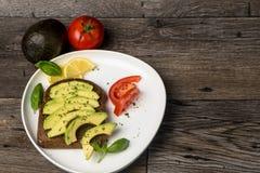 Avocadosandwich auf einer weißen Platte und einem Holztisch Lizenzfreies Stockbild