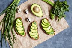 Avocadosandwiche mit Guacamolen und Spinat auf Pergamentpapier auf einem konkreten Hintergrund Frühlingslebensmittel Kohlenhydrat lizenzfreies stockbild
