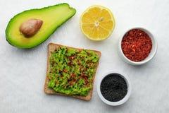 Avocadotoast gewürzt mit schwarzen Samen und Paprika des indischen Sesams lizenzfreie stockfotos
