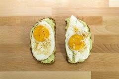 Avocadotoast und Spiegelei auf hölzernem Hintergrund zum Frühstück Lizenzfreie Stockfotos