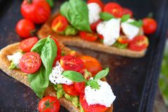 Avocadotoost caprese op donkere achtergrond royalty-vrije stock foto's
